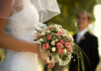 A bride wearing a white dress with her veil down holding a bouquet of pink and yellow roses.